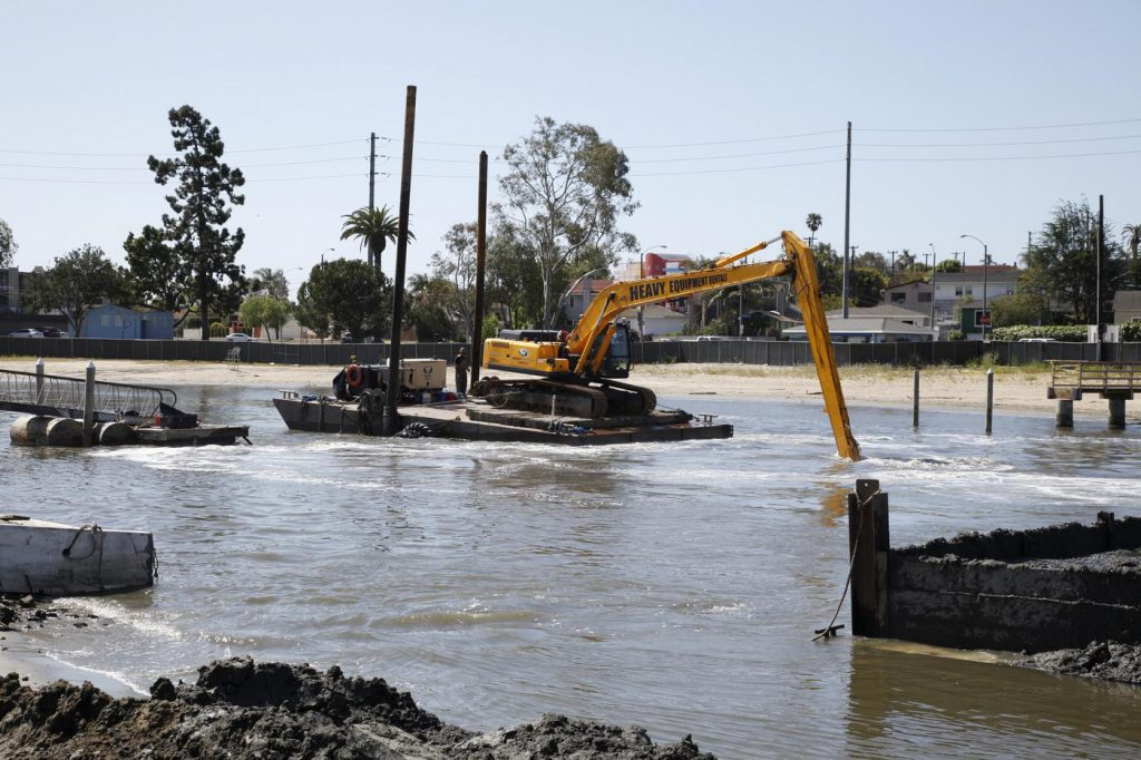 An excavator removes sediment from Colorado Lagoon